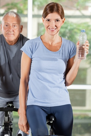 Smiling woman with water bottle on bike in fitness center Stock Photo - 12955806