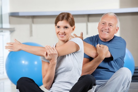 stretches: Senior people stretching their muscles in gym Stock Photo