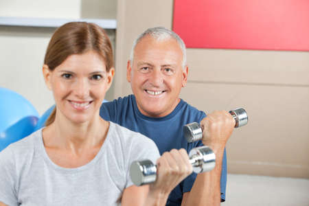 Two seniors lifting weights with dumbbells in fitness center photo
