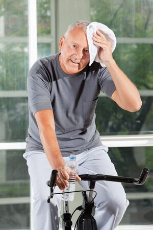 exhausted: Tired senior man on home trainer with towel in fitness center Stock Photo