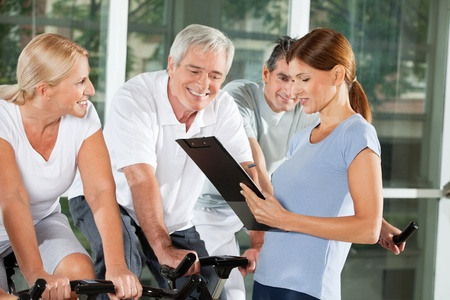 training wheels: Fitness trainer talking to senior citizens on bikes in gym Stock Photo