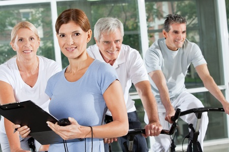 Fitness trainer coaching spinning exercise class with seniors in gym photo
