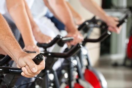 Beaucoup de mains sur les vélos de filage dans un centre de fitness Banque d'images