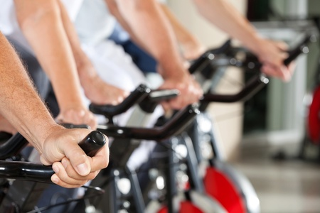 fitness center: Many hands on spinning bikes in fitness center