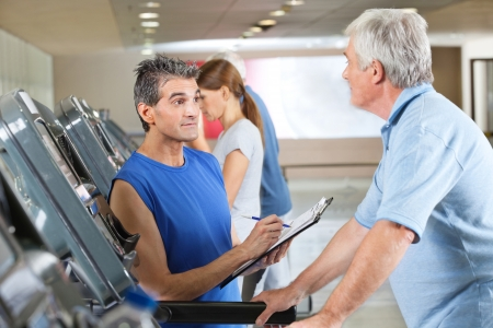 treadmill: Fitness trainer coaching elderly man on treadmill in gym Stock Photo