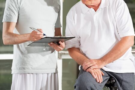 Fitness trainer in gym with clipboard creating training plan for senior man photo