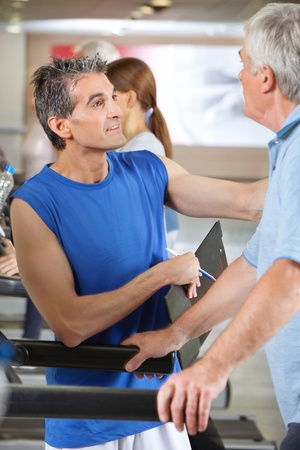Senior man on treadmill in gym talking to fitness trainer photo
