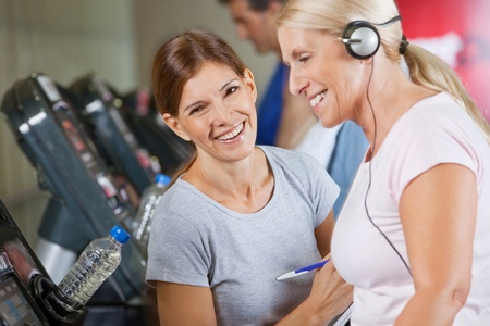Happy fitness trainer coaching senior woman in gym photo