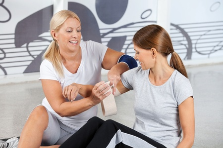 wrist pain: First Aid from fitness trainer in gym for woman with pain in her joints
