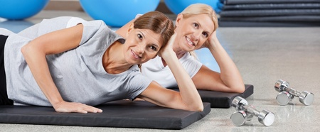 muscle formation: Two smiling women relaxing on gym mats in fitness center