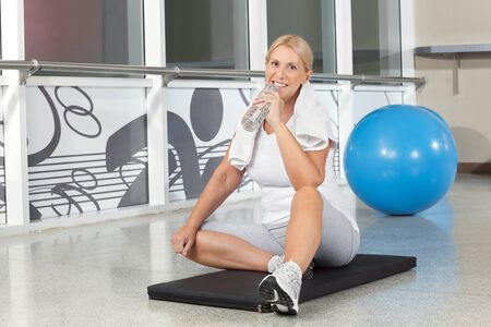 Smiling senior woman in gym drinking water from plastic bottle photo