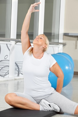 Senior woman doing breathing exercise in fitness center photo