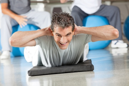 Happy man doing back exercises on gym mat in fitness center photo