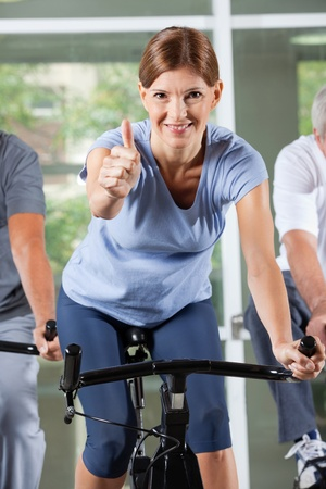Elderly woman in fitness center on spinning bike holding thumbs up photo