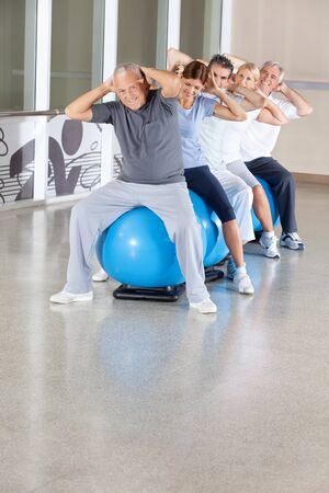 Senior citizens doing back exercises on gym ball in gym photo
