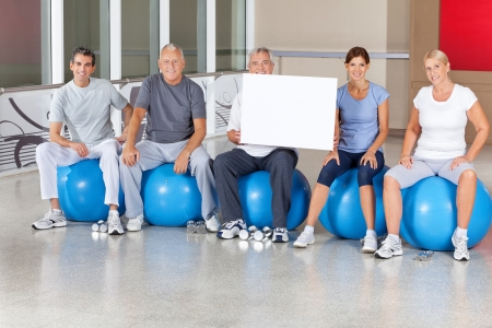Senior fitness group in gym with empty sign photo