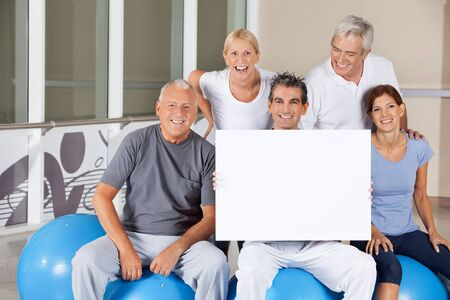 senior group: Happy senior people on gym balls holding empty poster in fitness center