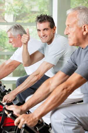 Happy senior man in gym on bike holding thumbs up photo