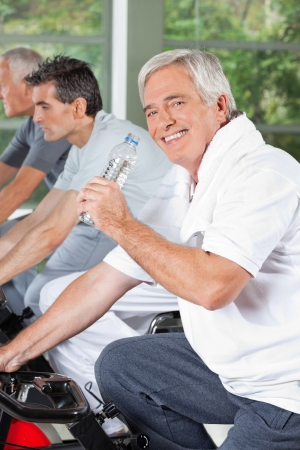 Smiling senior with water bottle in gym on bike photo