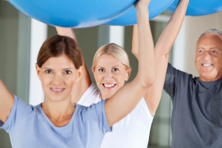 Happy seniors doing rehab exercises with gym balls in fitness center Stock Photo - 13054056
