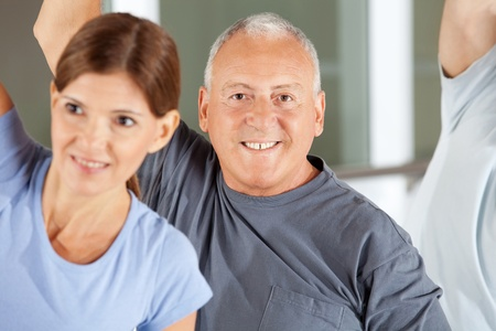 Portrait of happy senior man exercising in gym photo