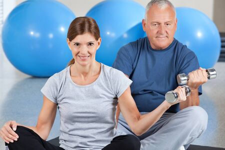 Man and woman doing a dumbbell training in gym photo