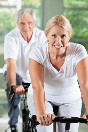 Happy senior people exercising on spinning bikes in gym photo