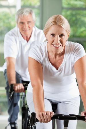 senior fitness: Happy senior people exercising on spinning bikes in gym