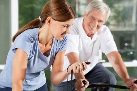 Woman in fitness center with stopwatch on spinning bike photo