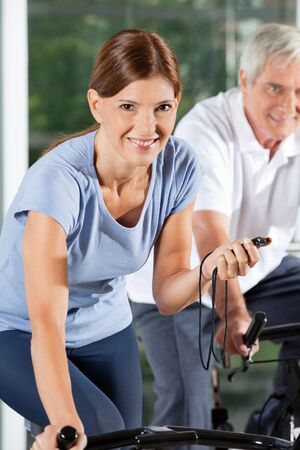 Happy woman with stopwatch in gym on spinning bike photo