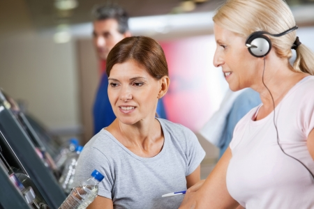 Fitness trainer talking to senior woman on treadmill in gym photo