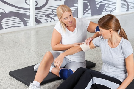 elbows: Woman with sports injury gets First Aid from fitness trainer in gym Stock Photo