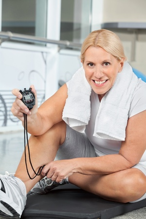 Happy senior woman showing stopwatch in gym photo