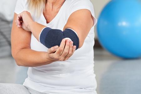 codo: Mujer con dolor en las articulaciones y un vendaje en el gimnasio Foto de archivo