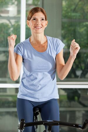 Cheering woman on bike in fitness center clenching her fists photo