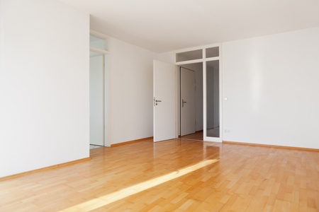 Empty room in apartment with parquet and white walls photo