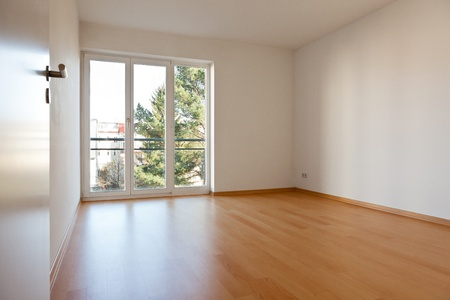 Empty room with parquet and white walls in an apartment photo