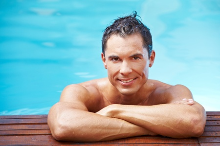 Young smiling man leaning at edge of swimming pool Stock Photo - 13560542