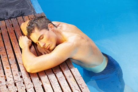 Young attractive man relaxing with eyes closed at edge of swimming pool photo