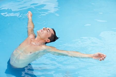 leaned: Young attractive man relaxing leaned back in ocean with blue water Stock Photo