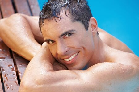Smiling happy attractive man in swimming pool with blue water Stock Photo - 13560613