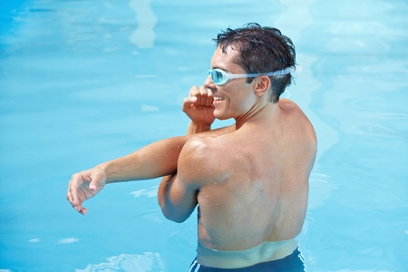 Attractive young man doing water aerobics in blue swimming pool photo