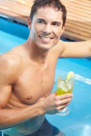 Young attractive man with cocktail in a swimming pool Stock Photo - 13560611