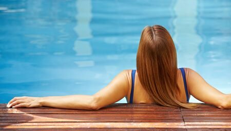 woman back view: Back view of relaxed woman in swimming pool with blue water