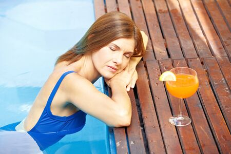 Relaxed elderly woman resting at edge of swimming pool with cocktail photo