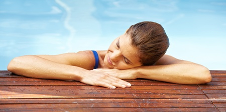 Attractive elderly woman resting at edge of swimming pool photo