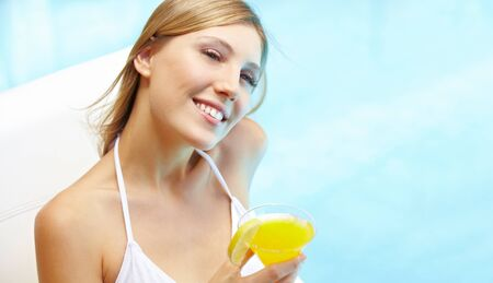 Beautiful young woman drinking a cocktail near the swimming pool in summer photo