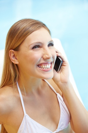 Happy smiling attractive woman using cell phone at swimming pool Stock Photo - 13559457