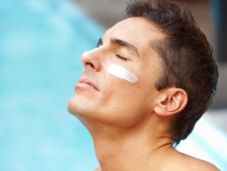 Attractive man sunbathing near pool with sunscreen on his face photo