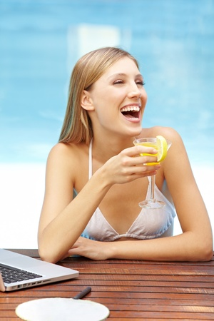 Laughing happy woman with cocktail in swimming pool photo